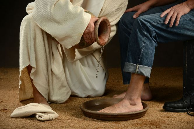 27941529 - jesus washing feet of modern man wearing jeans